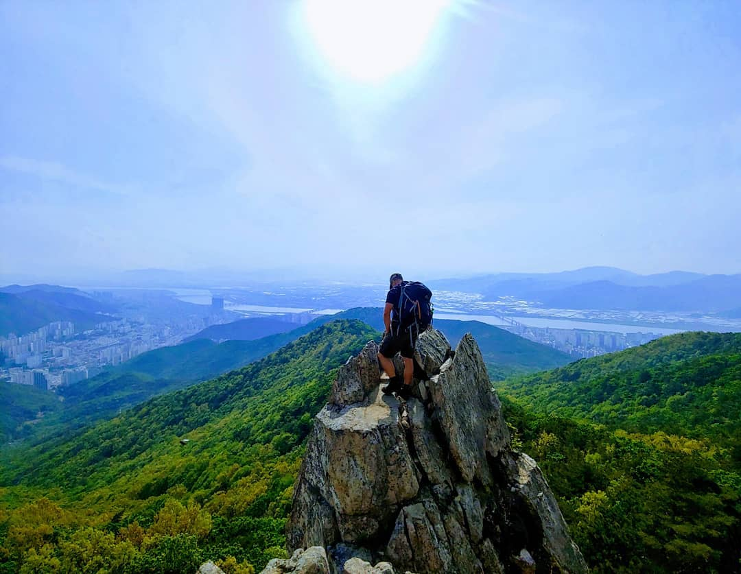 A photo of Bogue reaching the Summit of a mountain in Busan.